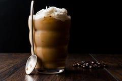 Café froid avec de la crème et lait fouetté, cuillère et grains de café photographie stock libre de droits
