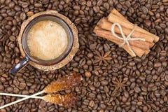 Café fuerte con la espuma, canela, palillo del azúcar en los granos de café Fotografía de archivo libre de regalías