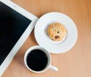 Café, galletas y tableta colocados en una tabla de madera el trabajo con se relaja Fotografía de archivo