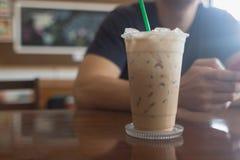 Café glacé avec le téléphone intelligent d'utilisation de l'homme comme fond Images stock