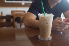Café glacé avec le téléphone intelligent d'utilisation de l'homme comme fond Photo libre de droits