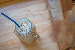Café glacé dans la cruche, tasses en verre de tasse sur le dessus de table en bois Images stock