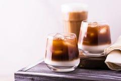 Café glacé en verres avec du lait Fond noir Photographie stock