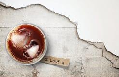 Café glacé et papier déchiré sur le plancher en béton criqué Photos libres de droits
