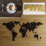 Café, granos de café y torta en una tabla de madera Foto de archivo libre de regalías