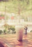 Café helado de la leche en taza plástica en la tabla de madera en backgrou del árbol Imagen de archivo