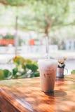 Café helado de la leche en taza plástica en la tabla de madera en fondo del árbol Foto de archivo libre de regalías