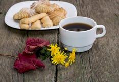 Café, hoja, florete y placa con las galletas detrás, una vida inmóvil Imagen de archivo libre de regalías