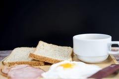 Café, huevo, jamón y pan calientes en la tabla de madera para el desayuno imágenes de archivo libres de regalías