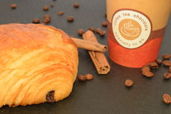 Café a ir y cruasán con los granos de café Imagen de archivo