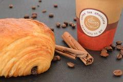 Café a ir y cruasán con los granos de café Imagenes de archivo