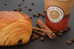 Café a ir y cruasán con los granos de café Foto de archivo