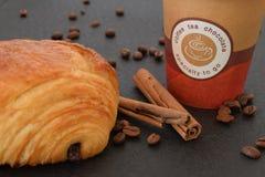 Café a ir y cruasán con los granos de café Fotografía de archivo