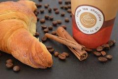 Café a ir y cruasán con los granos de café Imágenes de archivo libres de regalías
