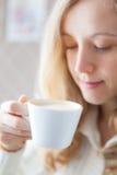 Café. Jovem mulher bonita que guardara à disposição uma chávena de café Fotografia de Stock Royalty Free