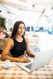 Café joven de la bebida del estudiante mientras que teclea en su ordenador portátil mientras que se sienta en café en el aire fre foto de archivo libre de regalías