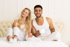 Café joven Juice Sitting In Bed anaranjado de la bebida de los pares, hombre hispánico joven y mujer de la sonrisa feliz Imagenes de archivo