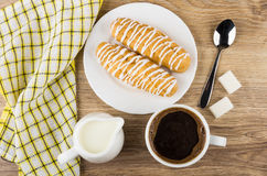 Café, lait de cruche, eclairs dans le plat, serviette, sucre et cuillère Photo stock