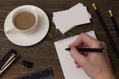 Café, libreta para tomar notas y la mano Foto de archivo
