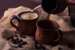 Café, mañana, concepto de los granos de café - coffe en taza de la loza de barro fotografía de archivo
