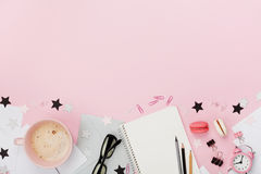 Café, macaron, fourniture de bureau, réveil et carnet frais sur la vue supérieure en pastel rose de table style plat de configura Images libres de droits