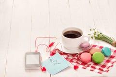 Café, macarrones y crema con una tarjeta de la buena mañana Fotos de archivo