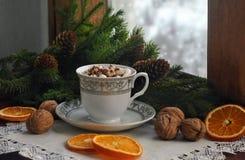Café, marshmallow, nozes, ramos de árvore do Natal perto de uma janela nevado de madeira Cartão do Natal e do ano novo Imagens de Stock