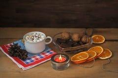 Café, melcocha, nueces, chocolate y una vela ardiente en una tabla de madera Tarjeta de la Navidad y del Año Nuevo Imagen de archivo