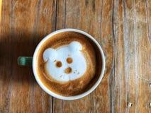 Café mignon d'art de latte de visage de chien dans la tasse blanche sur la table en bois Image libre de droits
