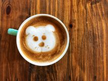 Café mignon d'art de latte de visage de chien dans la tasse blanche sur la table en bois Images libres de droits