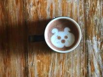 Café mignon d'art de latte de visage de chien dans la tasse blanche sur la table en bois Image stock