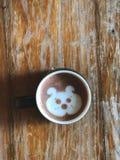 Café mignon d'art de latte de visage de chien dans la tasse blanche sur la table en bois Photographie stock