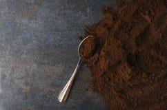 Café moído e colher na superfície cinzenta, tabela Conceito da preparação do café no café imagem de stock