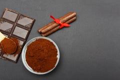 Café molido y chocolate en el fondo negro y el café llenado fresco en la cuchara de madera Foto de archivo