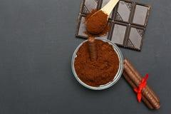 Café molido y chocolate en el fondo y el café llenado fresco en la cuchara de madera Foto de archivo