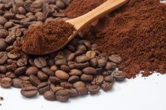Café molido y granos de café en el fondo y el spoo de madera foto de archivo