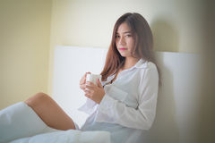 Café moreno hermoso de la consumición y de la mañana de la mujer en dormitorio Imagen de archivo libre de regalías