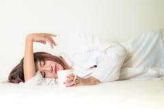 Café moreno hermoso de la consumición y de la mañana de la mujer en dormitorio Foto de archivo