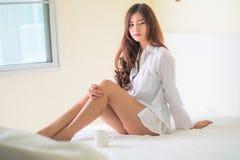 Café moreno hermoso de la consumición y de la mañana de la mujer en dormitorio Fotos de archivo