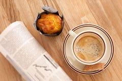 Café, muffin e um jornal imagem de stock