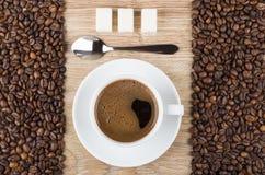 Café no copo, na colher, no açúcar na tabela de madeira e nos feijões Fotos de Stock