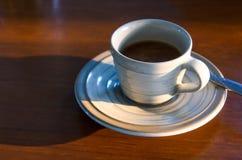 Café no copo na tabela perto da luz da janela Fotos de Stock