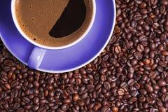 Café no copo roxo na tabela cercada com feijões de café fotografia de stock