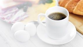 Café noir aromatique de tasse de plan rapproché et repas savoureux appétissant de petit déjeuner entourés par la lumière naturell banque de vidéos