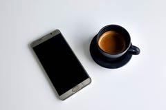 Café noir avec le téléphone intelligent sur la table blanche Photos libres de droits