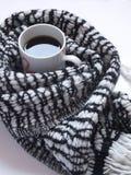 Café noir chaud avec l'écharpe noire et blanche modelée sur le bureau blanc Configuration plate Vue supérieure Images stock
