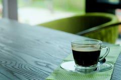 Café noir chaud d'Americano dans la table en bois en bois de la tasse la transparente avec le ton vert Photo libre de droits