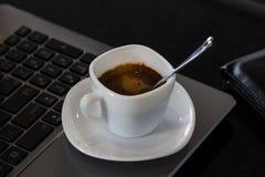 Café noir chaud dans la tasse blanche sur l'ordinateur portable au tabl fonctionnant photographie stock