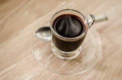 Café noir d'amoureux de fumée dans la tasse en verre Photos stock