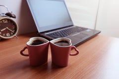Café noir dans des deux tasses de forme de coeur et ordinateur portable photographie stock